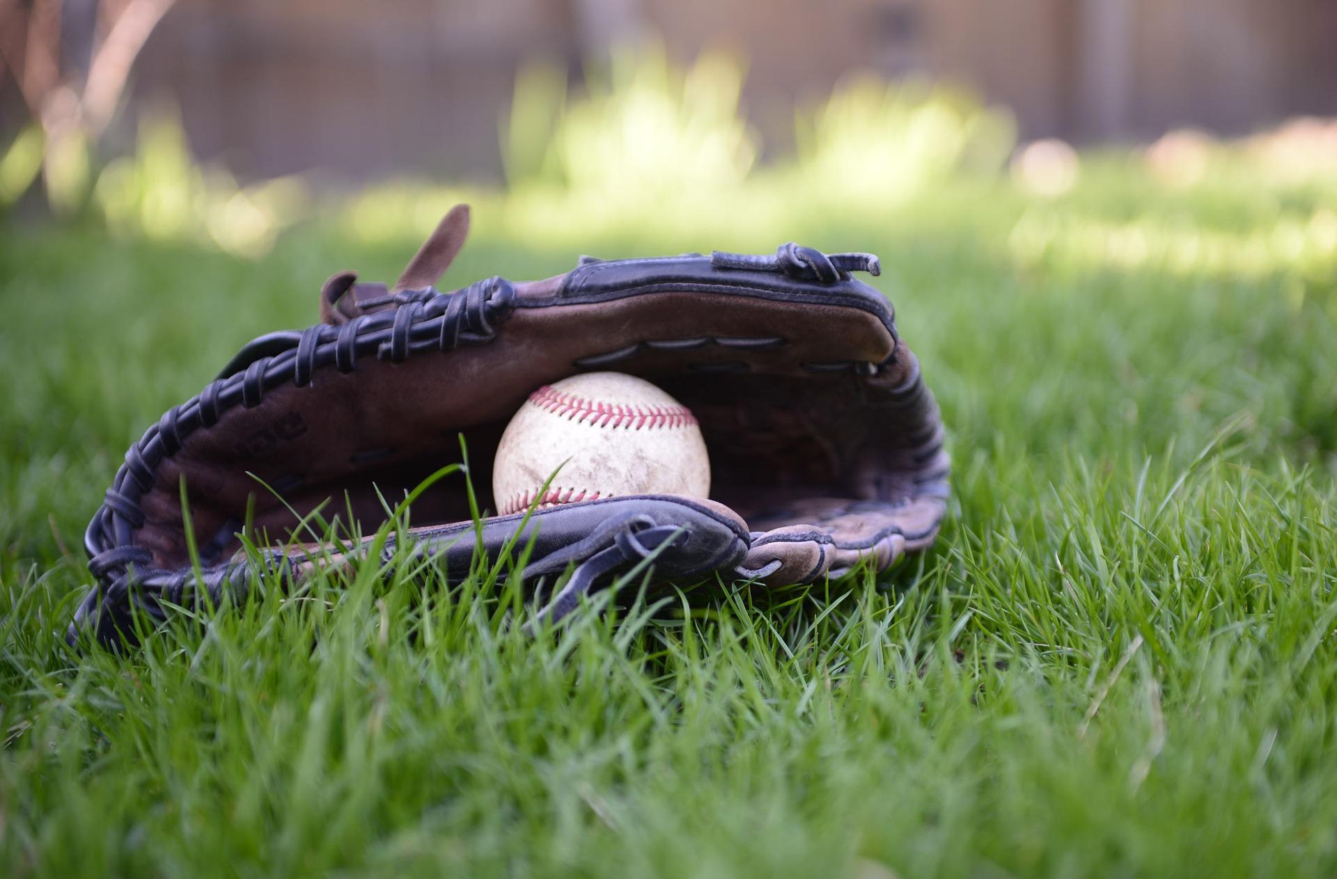 Gant et balle de baseball dans l'herbe